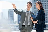 Businessman and businesswoman talking on urban balcony Stock Photo - Premium Royalty-Freenull, Code: 635-06191811
