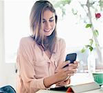 Smiling businesswoman checking cell phone Stock Photo - Premium Royalty-Freenull, Code: 635-06191837