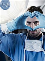 Portrait of surgeon making heart-shape with hands under surgical light Stock Photo - Premium Royalty-Freenull, Code: 635-06191880