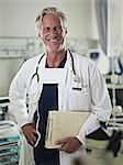 Portrait of smiling doctor holding medical record in hospital room Stock Photo - Premium Royalty-Freenull, Code: 635-06191898