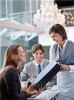 Waitress giving menu to woman in restaurant Stock Photo - Premium Royalty-Freenull, Code: 635-06192010