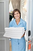 Portrait of smiling maid with towels in hotel room doorway Stock Photo - Premium Royalty-Freenull, Code: 635-06192025