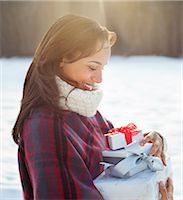 present wrapped close up - Smiling woman carrying Christmas gifts Stock Photo - Premium Royalty-Freenull, Code: 635-06192048