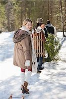 snow christmas tree white - Portrait of friends with sleds and fresh cut Christmas tree in woods Stock Photo - Premium Royalty-Freenull, Code: 635-06192069