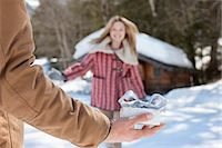 present wrapped close up - Woman running toward man holding Christmas gift in snow Stock Photo - Premium Royalty-Freenull, Code: 635-06192086
