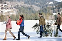 snow christmas tree white - Couples and dog carrying fresh cut Christmas tree and gifts in snow Stock Photo - Premium Royalty-Freenull, Code: 635-06192110