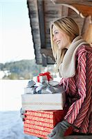 Smiling woman holding Christmas gifts on cabin porch Stock Photo - Premium Royalty-Freenull, Code: 635-06192121