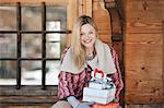 Portrait of smiling woman holding Christmas gifts on cabin porch Stock Photo - Premium Royalty-Free, Artist: Blend Images, Code: 635-06192135