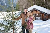 snow christmas tree white - Portrait of smiling couple with fresh cut Christmas tree in front of cabin Stock Photo - Premium Royalty-Freenull, Code: 635-06192138