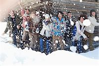 Portrait of smiling friends throwing snowballs in front of cabin Stock Photo - Premium Royalty-Freenull, Code: 635-06192156