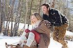 Smiling couple sledding in snow Stock Photo - Premium Royalty-Free, Artist: Blend Images, Code: 635-06192175