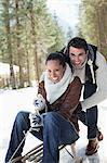 Smiling couple sledding in snowy woods Stock Photo - Premium Royalty-Free, Artist: Westend61, Code: 635-06192222