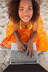 Young smiling woman looking up while using her laptop on her beach towel Stock Photo - Premium Royalty-Free, Artist: Water Rights, Code: 6109-06195255