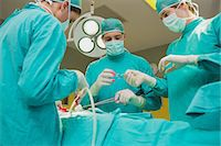 View of a male nurse giving a scissor to a surgeon Stock Photo - Premium Royalty-Freenull, Code: 6109-06195882