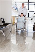 Smiling doctor wheeling a smiling girl in a wheelchair Stock Photo - Premium Royalty-Freenull, Code: 6109-06195984