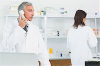 Pharmacist talking on the phone in a pharmacy with an other pharmacist Stock Photo - Premium Royalty-Freenull, Code: 6109-06196133
