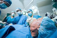 Surgerical team in an operating theater operating an unconscious patient Stock Photo - Premium Royalty-Freenull, Code: 6109-06196386
