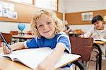 Smiling boy sitting at desk with exercise book Stock Photo - Premium Royalty-Free, Artist: Uwe Umstätter, Code: 6109-06196536
