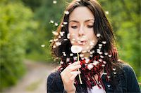 Girl blowing on white dandelion in the forest Stock Photo - Royalty-Freenull, Code: 400-06202868
