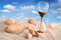 sand clock - Hourglass in the sand with blue sky Stock Photo - Royalty-Freenull, Code: 400-06203345