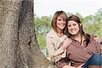 Portrait of Mother and Daughter Sitting by Tree
