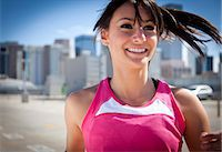Smiling Young Woman Running Outdoors Stock Photo - Premium Rights-Managednull, Code: 822-06302396