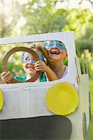 Boy and Girl Wearing Goggles Driving Cardboard Car Stock Photo - Premium Rights-Managednull, Code: 822-06302493