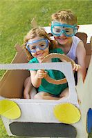 Boy and Girl Wearing Goggles Driving Cardboard Car Stock Photo - Premium Rights-Managednull, Code: 822-06302529