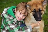 Boy Hugging Alsatian Puppy Stock Photo - Premium Rights-Managednull, Code: 822-06302606