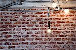 Illuminated Light Bulbs Hanging in front of Brick Wall Stock Photo - Premium Rights-Managed, Artist: ableimages, Code: 822-06302670