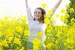 Smiling Teenage Girl with Arms Raised amongst Canola Flowers Stock Photo - Premium Rights-Managed, Artist: ableimages, Code: 822-06302673