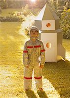 Boy Wearing Space Suit Standing in front of Cardboard Rocket Spacecraft Stock Photo - Premium Rights-Managednull, Code: 822-06302730