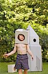 Boy Wearing Homemade Cardboard Helmet Playing in front of Rocket Spacecraft