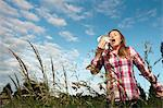 Woman sneezing in tall grass Stock Photo - Premium Royalty-Freenull, Code: 649-06304861
