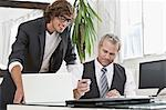 Businessmen working together at desk Stock Photo - Premium Royalty-Free, Artist: Cultura RM, Code: 649-06305271