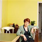 Woman sitting at kitchen table Stock Photo - Premium Royalty-Free, Artist: Cultura RM, Code: 649-06305322