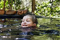 Boy swimming in river in forest Stock Photo - Premium Royalty-Freenull, Code: 649-06305349