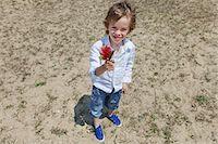 Boy holding flower on grassy beach Stock Photo - Premium Royalty-Freenull, Code: 649-06305525