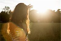 Woman shielding her eyes from sun Stock Photo - Premium Royalty-Freenull, Code: 649-06305544