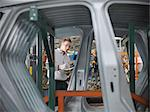 Worker inspecting car parts in car factory