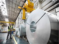 Worker operating crane with steel rolls in car factory Stock Photo - Premium Royalty-Freenull, Code: 649-06305678