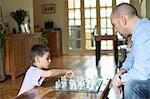 Father and son playing chess together Stock Photo - Premium Royalty-Free, Artist: Blend Images, Code: 649-06305733