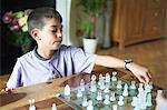 Boy playing chess in living room Stock Photo - Premium Royalty-Free, Artist: Artiga Photo, Code: 649-06305737