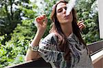 Woman smoking on balcony outdoors Stock Photo - Premium Royalty-Free, Artist: Beth Dixson, Code: 649-06305775