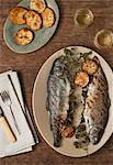 Grilled Trout Stuffed with Lemon and Parsley on a Platter; Oven Roasted Potatoes and White Wine Stock Photo - Premium Royalty-Freenull, Code: 659-06307235