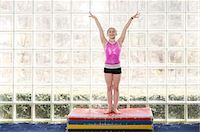 preteen girls gymnastics - young gymnast holding hands in air, smiling Stock Photo - Premium Royalty-Freenull, Code: 6106-06308082