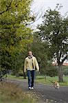 Young man walking dog Stock Photo - Premium Royalty-Freenull, Code: 6106-06309045