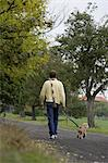 Young man walking dog Stock Photo - Premium Royalty-Free, Artist: Aurora Photos, Code: 6106-06309046