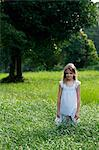 Young girl in white dress in grassy field
