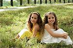 two young girls sitting in field